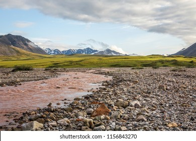 Standing alongside a storm swollen river looking across the arctic tundra with its permafrost palsas towards the remote mountains of the Gates of the arctic National Park. Galbraith Lake, Alaska.