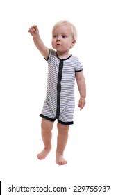 Standing baby boy looks and his hand forward. Isolated on white background