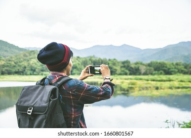 Standing back the Asian man using Camera smartphone Selfie taken of yourself connected to digital camera shooting photo Mountain river landscape. Traveling, Hiking concept.