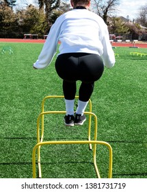 Standing behind a teenage girl jumping over two foot yellow hurdles wearing blak spandex and a white sweatshirt at track and field practice.