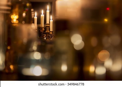 Standing brass chandelier with burning candles in shallow focus home setting.