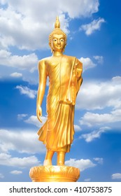 standing buddha image in the temple with clouds and blue sky