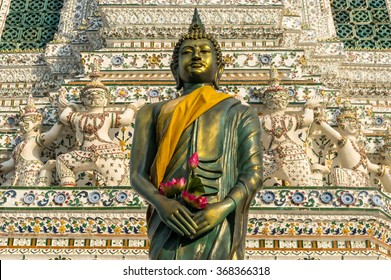 Standing Buddha sculpture wrapped in golden robe, kasaya, with lotus flowers placed in its hands. Wat Arun, Temple of Dawn, Bangkok, Thailand