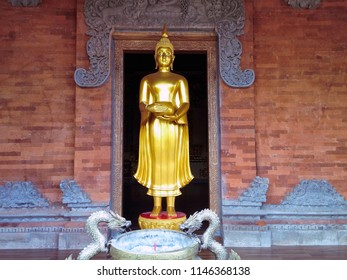 Standing Buddha Statue Carrying Jug At The Front Of Worship Room At Brahmavihara Arama Monastery, North Bali, Indonesia