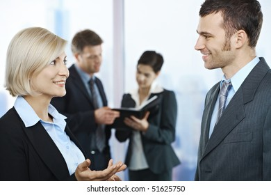Standing business people talking in office smiling at each other, coworkers looking at documents in background.