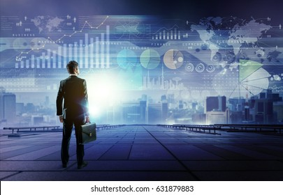 standing businessman who looks various graphics of business. Internet of Things. Information Communication Technology. Digital transformation. Abstract mixed media.