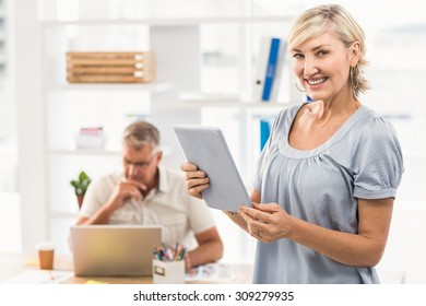 Standing businesswoman holding a tablet at the office