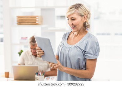 Standing businesswoman scrolling on a tablet at the office