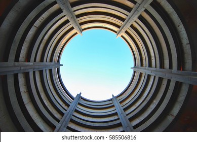 Standing in the center of a concrete parking garage ramp looking straight up with a clear blue sky beyond