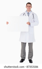 Standing doctor holding a sign to his right on white background