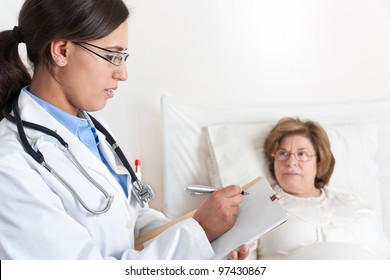 Standing Doctor writes prescription to Senior Patient lying in bed