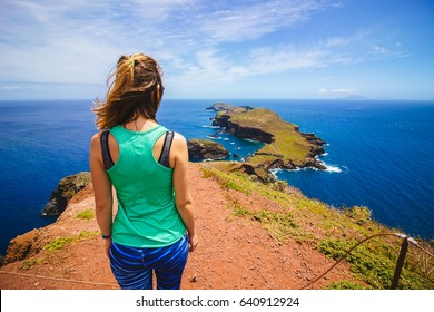 Standing at the end of a cliff overlooking a cape in Madeira with the Atlantic ocean in the background