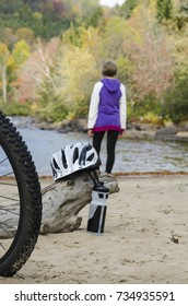 standing female bicyclist admires beautiful autumn landscape in foggy morning during halt at sand beach of riviere-rouge river by corridor aerobique bicycle trail in province of quebec, canada