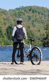 standing female bicyclist wearing helmet and backpack admires beautiful early autumn landscape in sunny morning during halt at sand beach, Riviere-Rouge, Corridor Aerobique, Quebec, Canada