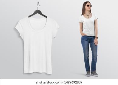 Standing female model wearing short sleeve white t shirt in blue denim jeans pant with sunglasses hand in pocket beside handing t shirt on hanger