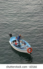 standing fisher in a boat