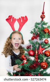 Standing girl puts decorations to a Christmas tree.