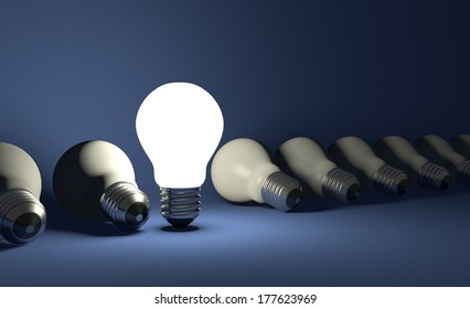 Standing glowing light bulb in row of lying switched off ones on dark blue textured background
