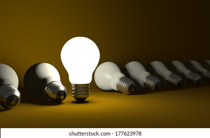 Standing glowing light bulb in row of lying switched off ones on dark yellow textured background