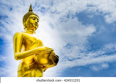 Standing Golden Buddha with sky in background