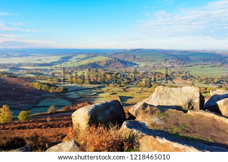 Standing high on Curbar Edge in the Derbyshire Peak District on an autumh morning looking out over the countryside.