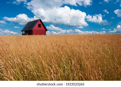 Standing house of bars stands in a field against the background of autumn grass and blue sky with clouds.