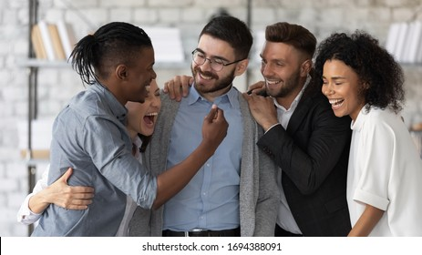 Standing and hugging smiling team laughing looking at each other. Happy diverse corporate staff, laughter specialists, company representatives, bank workers photo shoot, HR agency recruitments.