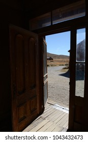 Standing inside a building in Bodie, California while looking outside through an open door.