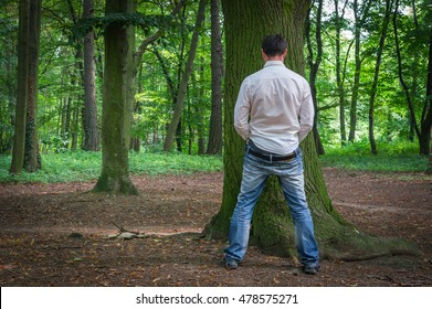 Standing man peeing near big tree in summer forest in nature - incontinence concept