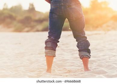 Standing man peeing on sand beach.