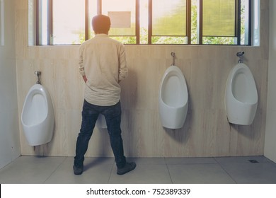 Standing man peeing to a urinal in restroom or incontinence concept soft focus.