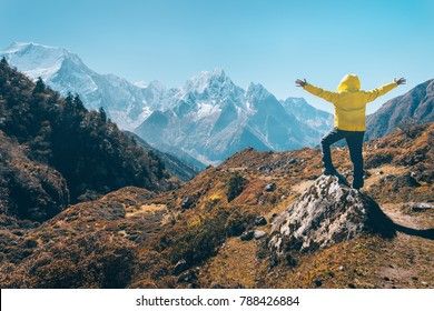 Standing man with raised up arms on the stone and looking on snow covered mountains. Landscape with traveler, high rocks with snowy peaks, grass, trees in autumn in Nepal. Lifestyle, travel. Trekking