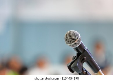Standing microphone for speaker's speech in the seminar room with audience in the background
