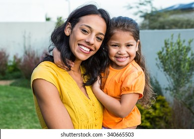 Standing mother holding her daughter outdoors posing for the camera