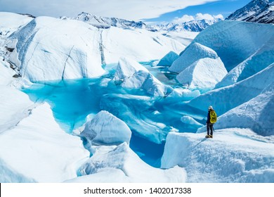 Standing near the edge of large blue pool on top of the Matanuska Glacier. A young woman holding an ice axe with a backpack and helmet looks out over the lake.