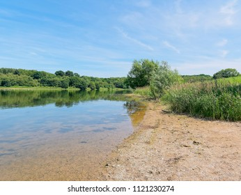 Standing on the banks of Staunton Harold Reservoir, in Derbyshire, the clear calm water reflects the surroundng countryside.
