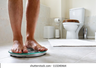 Standing on bathroom scale concept for dieting, slimming or overweight