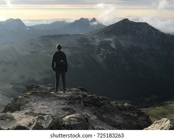 Standing on the edge of a cliff overlooking the Northern parts of the Cascade Mountain Range in Mount Rainier National Park towards the sunset and within Golden Hour.