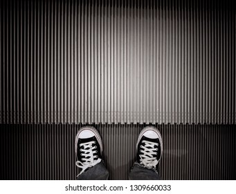 Standing on the escalator floor with copy space.vertical pattern with sneakers on stairs.striped metallic lines abstract background which has black and white color
