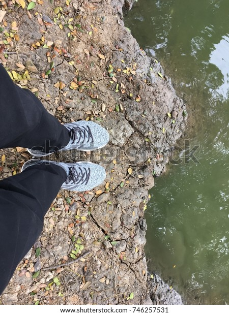 Standing on the ground beside riverbank