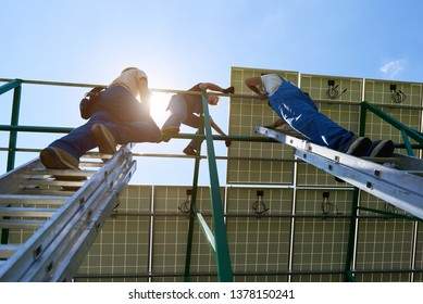 Standing on high ladders, workers team installing solar batteries screen. Using special equipment, wearing protective helmet. Environment friendly,resources saving, using renewable solar electricity.