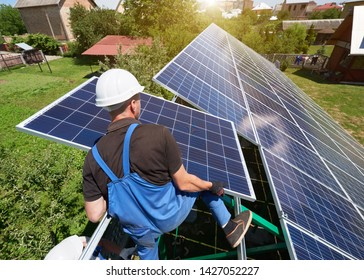 standing on high metallic ladder, worker keeping solar panel. installing solar batteries screen on house's roof. Modern solution for natural resources saving, using renewable solar energy. High-tech.