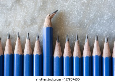 Standing out of the crowd. Being different concept. A row of perfect pencils with one broken. A symbol of disfigurement.