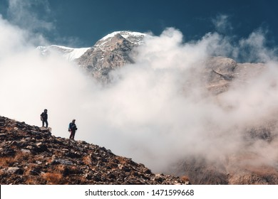 Standing people on the mountain trail in low clouds. Landscape with man and woman with backpacks on the hill, high mountain with snowy peak, blue sky. Travel in Nepal. Trekking and hiking. Nature