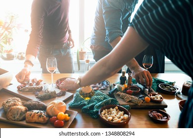 standing people picking up tapas food form a table. Friends and family  togetherness concept.