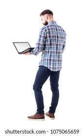 Standing professional business man holding and using laptop computer with blank screen. Full body isolated on white background.