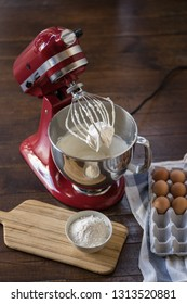 standing red mixer kitchen aid with cream on whisk. wooden table. vertical