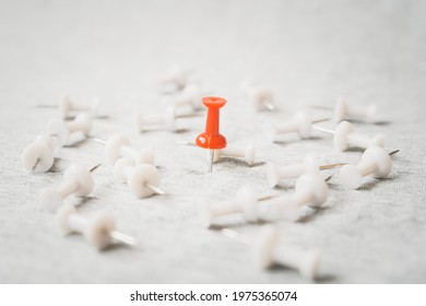 standing red thumbtack among blurred  white thumbtacks on grunge grey background , for outstanding leader, winner , strongest ,success , the best things or idea, winner among loosen concept