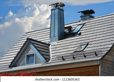 Standing Seam Steel Chimneys with High Grade Steel Cap, Roof Windows, Snow Guard and Dormer Window at a grey tiled Roof