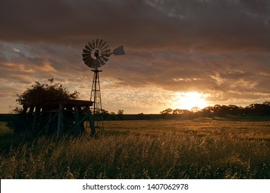 Standing in the setting sun an old broken windmill and tank stand in a farm field near Bacchus Marsh, rural Victoria, Australia.